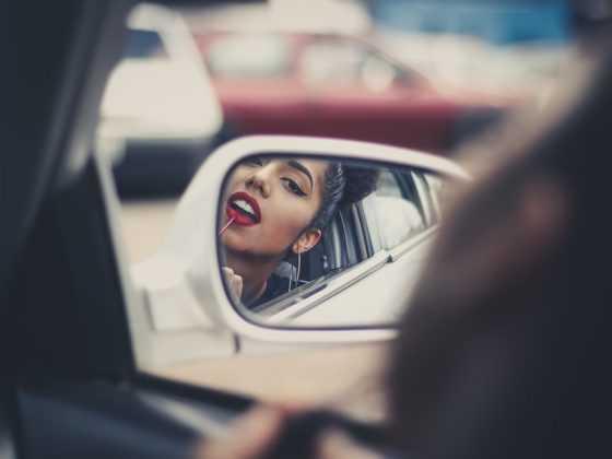 Девушка красит губы в зеркальце машины