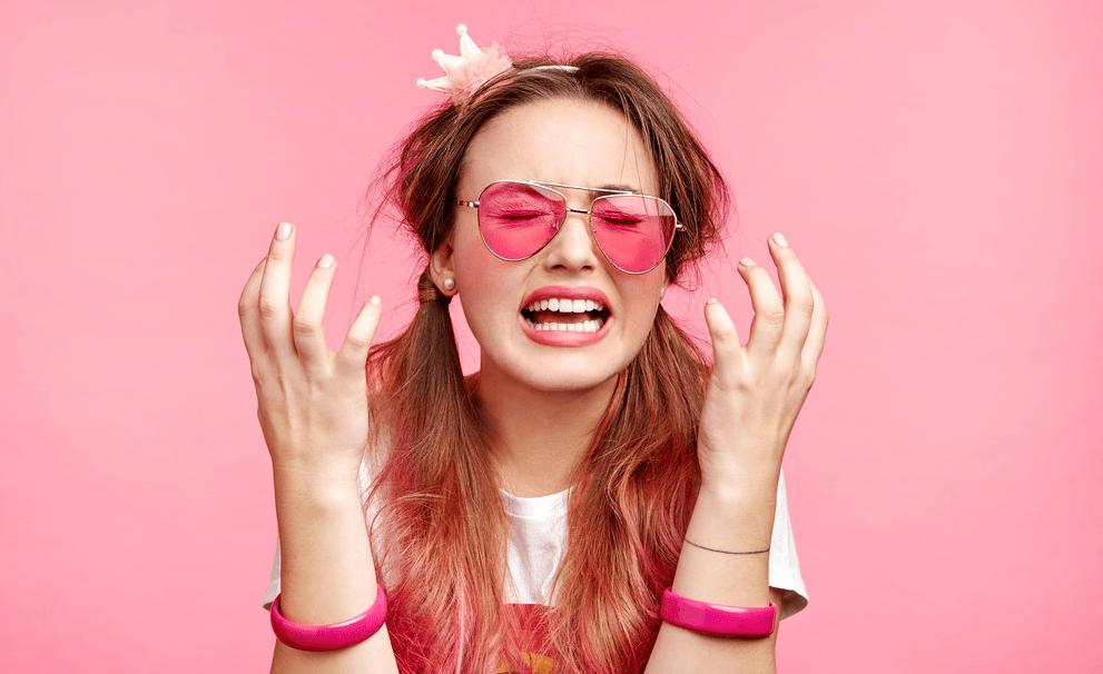 Девушка в розовом с короной на розовом фоне разводит руками