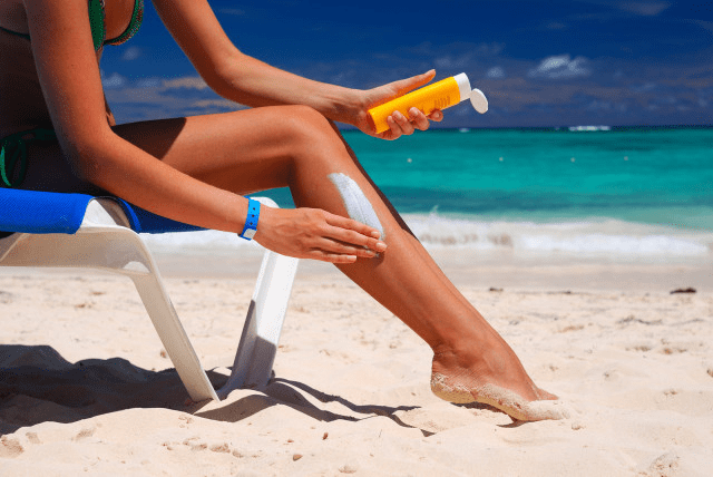 Девушка мажет ноги солнцезащитным кремом