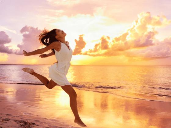 Девушка бежит по пляжу на фоне заката