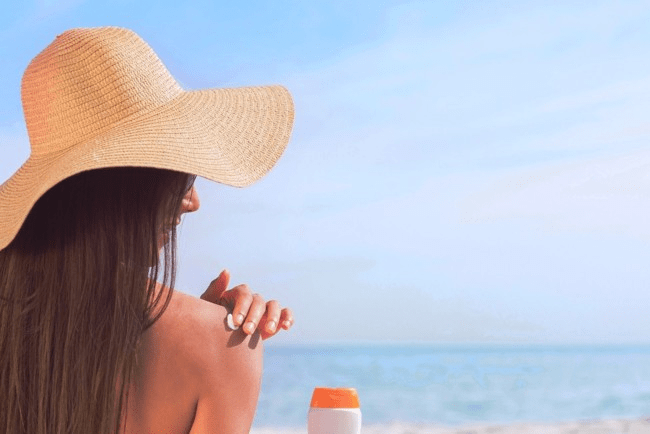 Девушка в шляпе на пляже мажется кремом