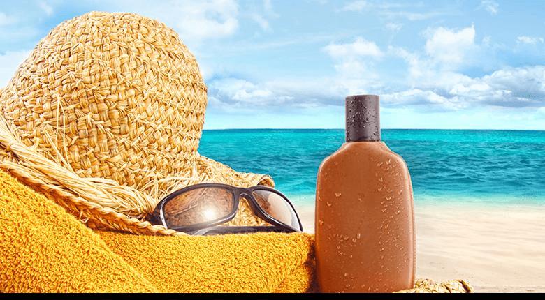 Шляпка, очки и солнцезащитный крем на пляже