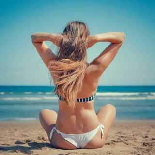 Девушка сидит на песке лицом к морю